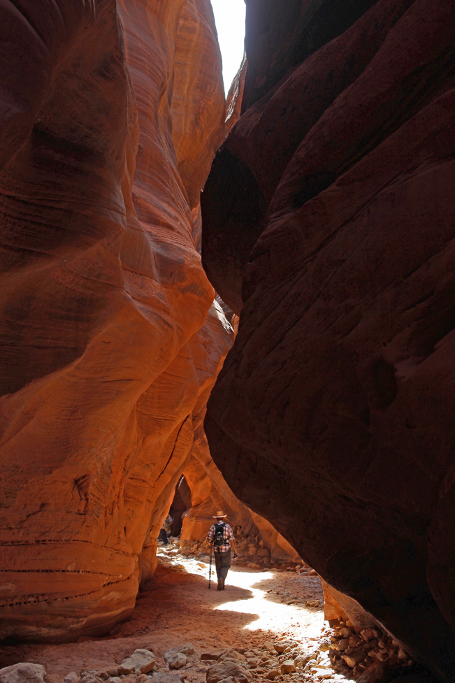 A hiker under a shaft of light, in Buckskin Gulch, in Vermillion Cliffs National Monument, Utah. Accessed from Wire Pass Hiking Trail. Easy Hikes. Grand Canyon Area