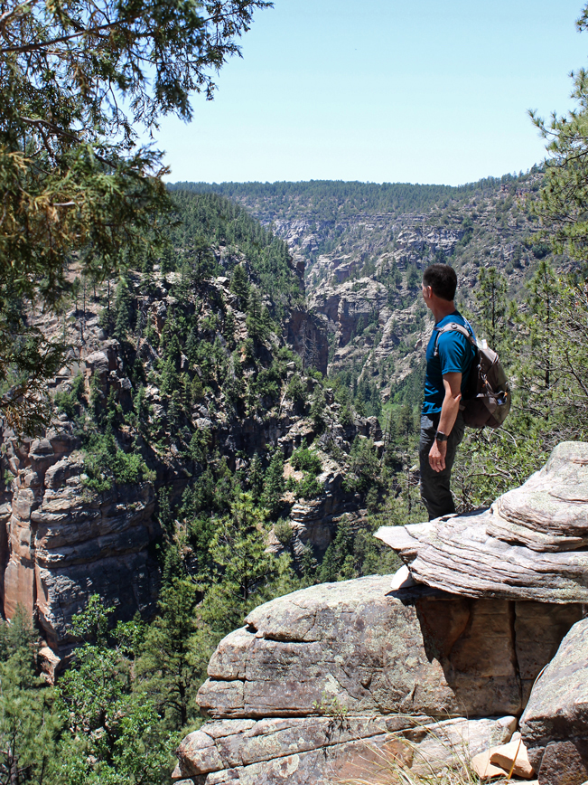 A landscape view of a hiker standing at the top of West Clear Creek Canyon, on the Maxwell Hiking Trail, with views of the canyon behind him. Outside of Flagstaff and Strawberry, Arizona. Moderate Arizona hiking trails. Flagstaff area hiking trails. Arizona hiking trails with water. Copyright AZUtopia. No use without permission.