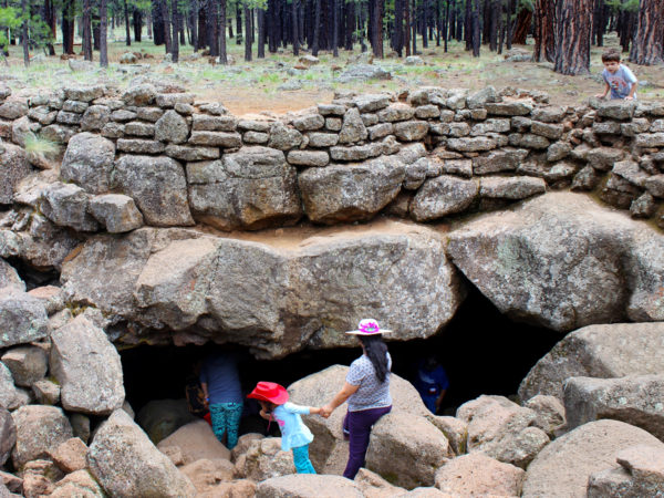 A family standing on the boulders outside the opening of the Lava River Tube, on the Lava River Tube Trail, near Flagstaff, Arizona. Easy Arizona hiking trails. Flagstaff area hiking trails. Arizona family friendly hiking trails. Copyright azutopia. No use without permission.