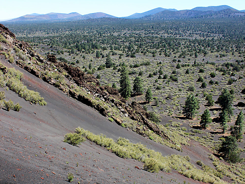 Landscape view of the loose lava on the side of Strawberry Crater; north of Flagstaff; Arizona. With the Sunset Crater Mountains in the distance. Taken from the Strawberry Crater Hiking Trail Loop. Copyright azutopia. No use without permission.