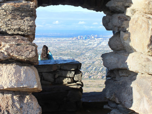 A hiker looking over downtown Phoenix, from Dobbins Lookout, at the top of the Holbert Hiking Trail, in South Mountain Park, Phoenix, Arizona. Stone structure, View, Moderate Hiking Trails, Phoenix Area Hiking Trails. copyright azutopia.com. No use without permission.