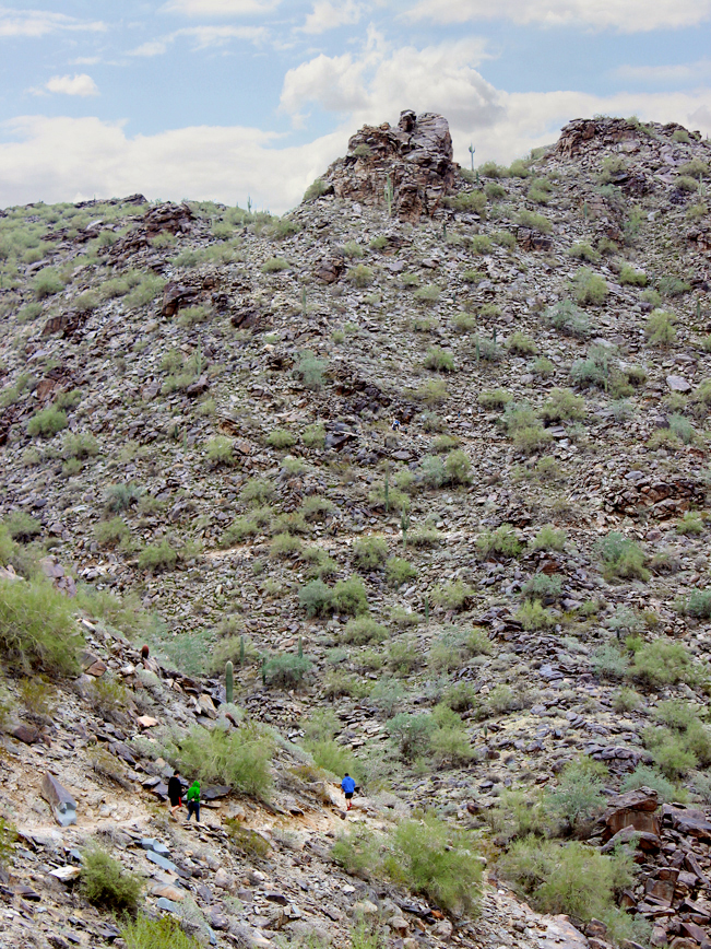 A landscape view of Hikers on the Holbert Hiking Trail to Dobbins Lookout, in South Mountain Park, Phoenix, Arizona. With a gap in the boulders above. Moderate Hiking Trails, Phoenix Area Hiking Trails. Copyright azutopia.com. No use without permission.