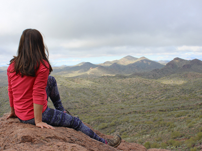 A female hiker sitting on a boulder near the top of Vulture Peak, on the Vulture Peak Hiking Trail, in Wickenburg, Arizona, northwest of Phoenix, with long views of the desert around her. Moderate Hiking Trails, Central Arizona Hiking Trails. Copyright AZUtopia. No use without permission.