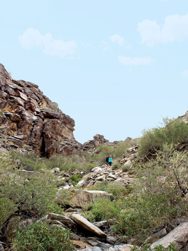 A landscape view of Hikers on the Holbert Hiking Trail to Dobbins Lookout, in South Mountain Park, Phoenix, Arizona. And beside some of the rocky cliffs. Moderate Hiking Trails, Phoenix Area Hiking Trails. Copyright azutopia.com. No use without permission.