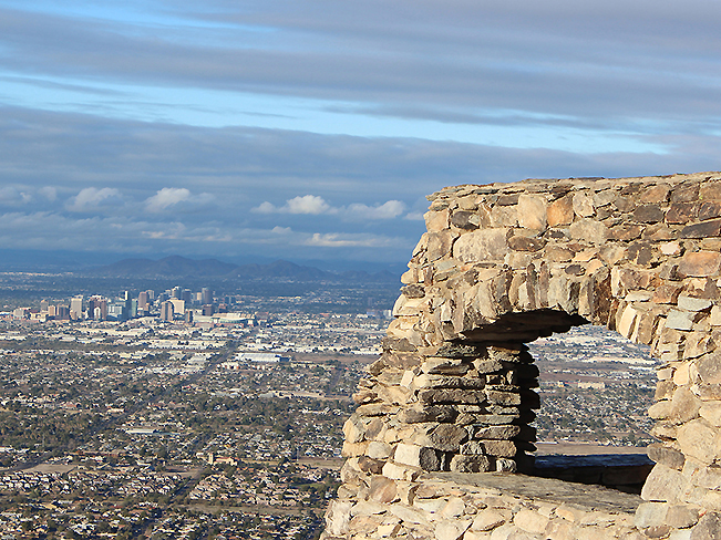 A panoramic view over downtown Phoenix, from Dobbins Lookout, at the top of the Holbert Hiking Trail, in South Mountain Park, Phoenix, Arizona. Stone structure, View, Moderate Hiking Trails, Phoenix Area Hiking Trails. copyright azutopia.com. No use without permission.