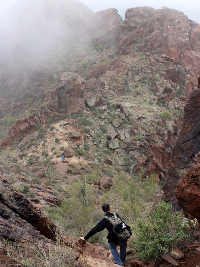A male hiker descending the steep rock scramble from the top of the craggy cliffs of Vulture Peak. With hikers on the Vulture Peak Hiking Trail below. In Wickenburg, Arizona, northwest of Phoenix. Moderate Hiking Trails, Central Arizona Hiking Trails. Copyright AZUtopia. No use without permission.