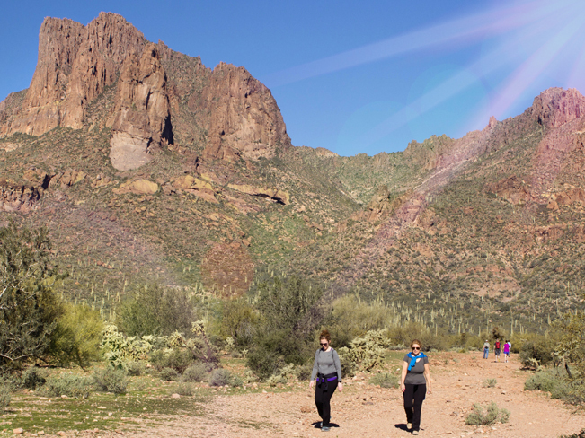 A landscape view of hikers at the base of the Wave Cave Hiking Trail with the cave and the Superstition Mountains in the background. Near Gold Canyon, Arizona. Moderate Hiking Trails, Phoenix Area Hiking Trails. Copyright AZUtopia. No use without permission.