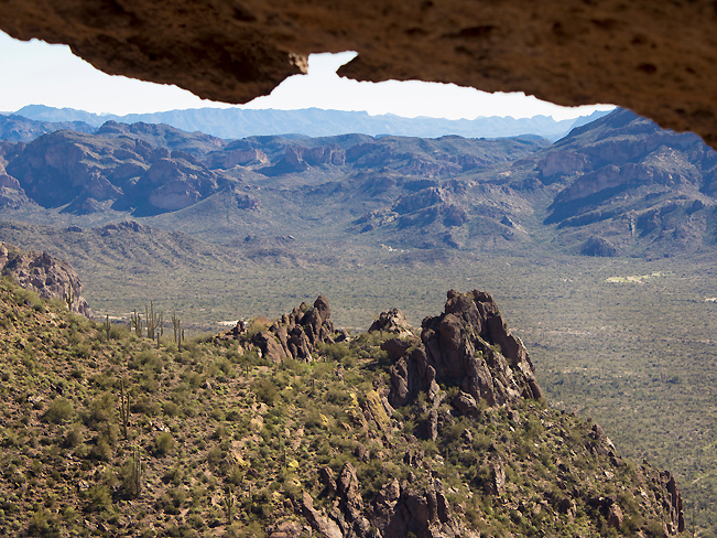A landscape view of the Superstition Mountains and Peralta Valley taken from inside the Wave Cave, at the top of the Wave Cave Hiking Trail. In the Superstition Mountains. Near Gold Canyon, Arizona. Moderate Hiking Trails, Phoenix Area Hiking Trails. Copyright AZUtopia. No use without permission.