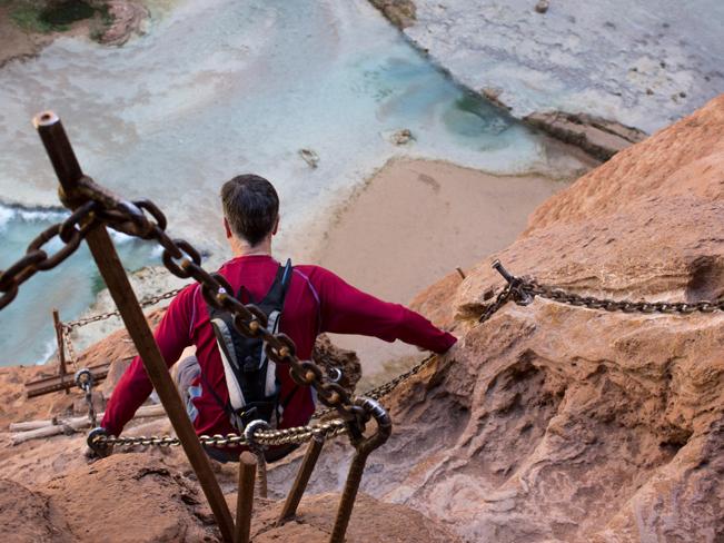 Hiker; Descent; Chains; Cliff; Havasu Hiking Trail; Havasupai Reservation; Havasu Canyon; Grand Canyon; Supai Village; Mooney Falls; Havasu Creek; Waterfall; Difficult Hiking Trails; Northern Arizona Hiking Trails; Copyright azutopia.com. No use without permission.