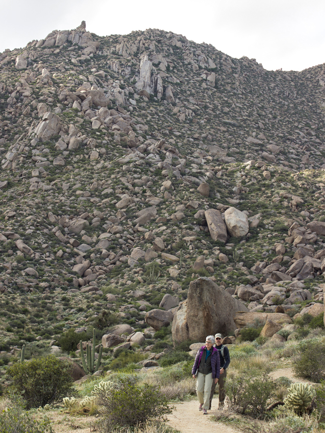 Hikers on Marcus Landslide Hiking Trail; at base of Boulder filled mountain; Large Rock Formations; McDowell Mountain Preserve; Phoenix; Arizona; Marcus Landslide Hiking Trail; Boulders; Hill; Mountains. Copyright azutopia.com. No use without permission.