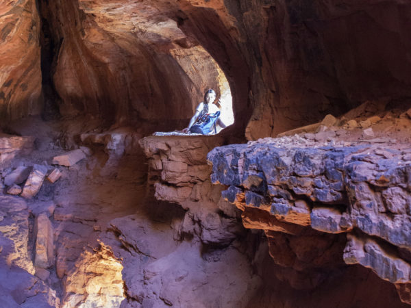 Young Woman with backpack; Hiker; Sitting inside cave; in front of opening; Redrocks; Cliffs; Crevice; Bright light; Soldiers Pass Hiking Trail; Soldiers Pass Caves; Sedona; Arizona; Northern Arizona Hiking Trails; Difficult Hiking Trails; Copyright azutopia.com. No use without permission.