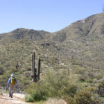 Landscape view of Hikers approaching Thompson Peak with Satellites towers on top; Blue sky; Thompson Peak Road:; Thompson Peak Hiking Trail; McDowell Mountains; Phoenix Area Hikes; Difficult Hikes; Fountain Hill; Arizona. Copyright azutopia.com. No use without permission.