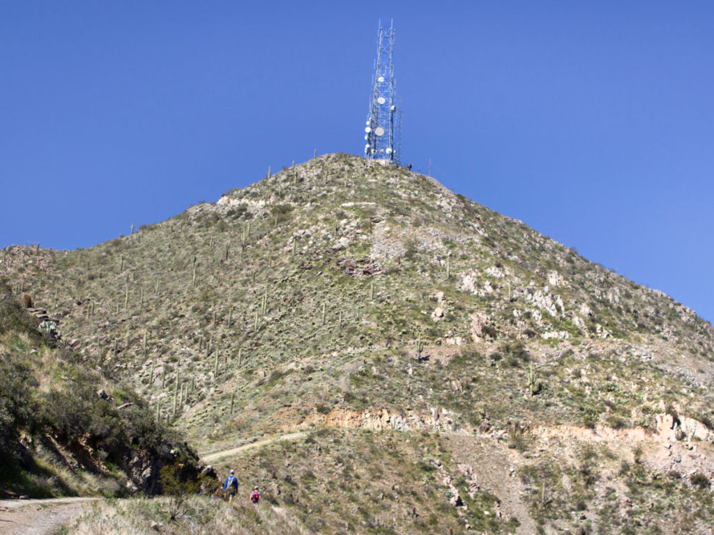 Hikers approaching the top of Thompson Peak; on the Thompson Peak Hiking Trail in the McDowell Mountains; Satellite Towers crown the peak. Phoenix Area Hikes; Difficult Hikes; Fountain Hill; Arizona. Copyright azutopia.com. No use without permission.