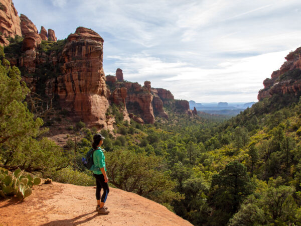 Landscape view of a hiker taking in the view, from the back of Fay Canyon in Sedona, Arizona's, with red rock formations, cliffs, trees and shrubs, Bell and Cathedral Rocks visible in the distance. Fay Canyon Hiking Trail, Easy Hiking Trails; Northern Arizona Hiking Trails, Family Friendly Hiking Trails, Copyright azutopia.com. No use without permission.